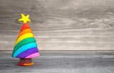 Fototapeta Tęcza - Playful Christmas concept. Handmade miniature Christmas tree in rainbow colors. Soft wood background. Plenty of free space to write text.