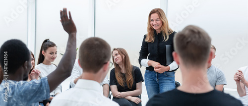 young woman standing in a circle of her colleagues.