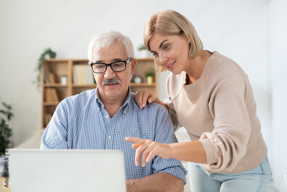 Fototapety, obrazy: Young woman pointing at laptop display while explaining something to her father