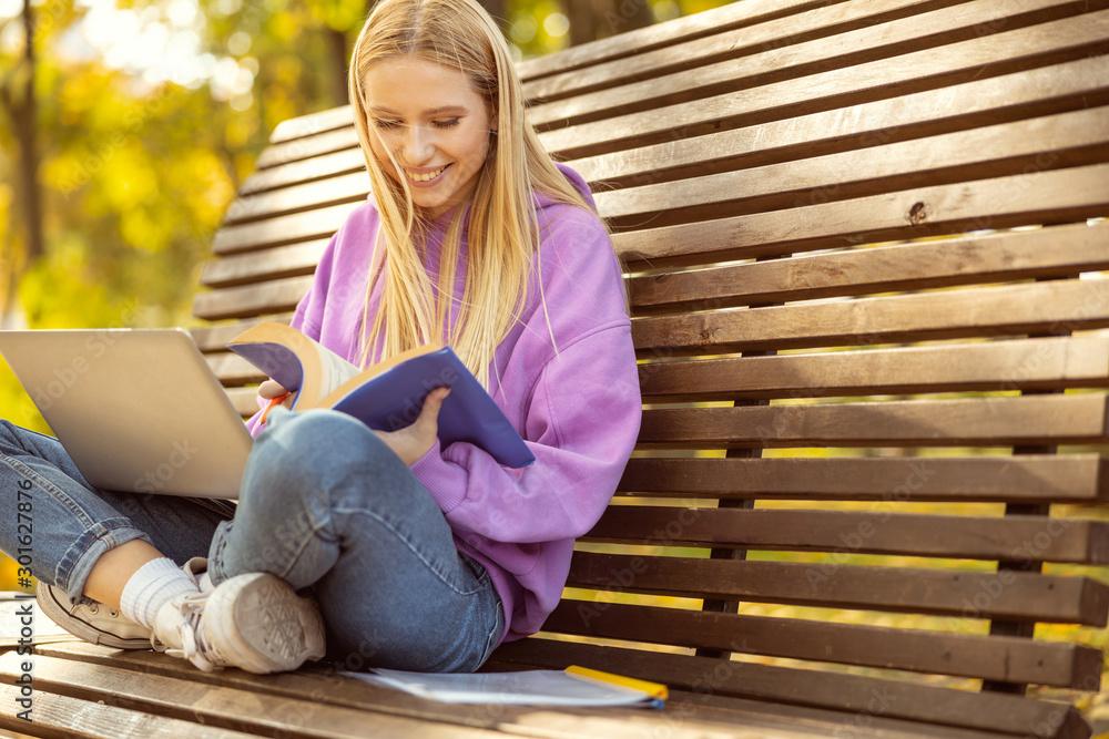 Fototapeta Positive delighted girl doing home task in park