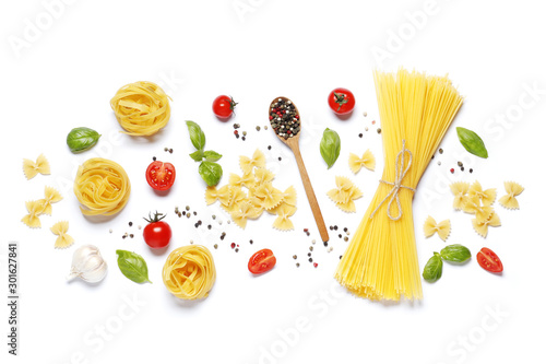 Fotografía  Flat lay composition of raw different pasta, fettuccine balls, cherry tomatoes,  spices, basil, olive oil, garlic isolated on a white background