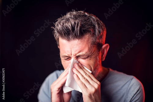 Valokuvatapetti Sick man has a runny nose and snot in napkin