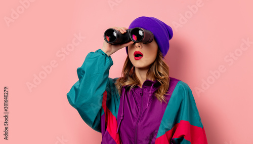 Valokuva Young woman in purple hat and 90s clothes with bonoculars on pink background