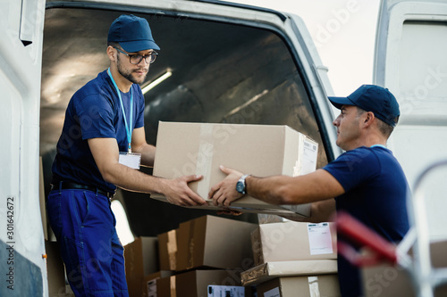 Valokuva Young couriers cooperating while unloading packages from delivery van