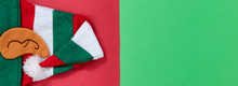 Bright Red And Green Background With Elf Cap For Christmas Season