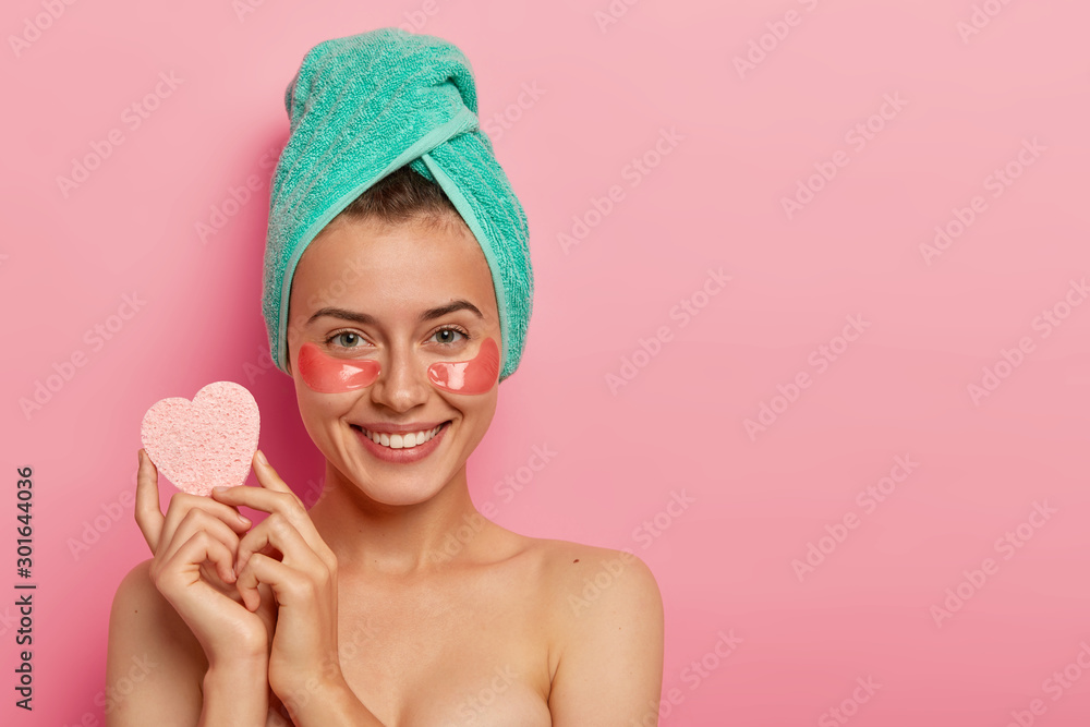 Fototapety, obrazy: Young happy woman wears collagen moisturizing patches under eyes, holds sponge for removing makeup, has beauty treatments, has fresh skin after taking shower, poses against rosy studio background