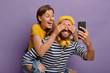 canvas print picture - Happy girlfriend rides piggyback, has fun with boyfriend covers his eyes, prepares surprise. Cheerful hipster holds smartphone in front, wears headphones around neck. Couple foolishing around
