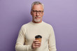 canvas print picture - Grey haired senior man wears transparent glasses and white sweater, stands and cools hot beverage, enjoys pleasant conversation, poses against purple background. People, age, lifestyle concept