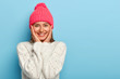 Romantic positive young European woman smiles gently, has white perfect teeth, touches both cheeks, has friendly look, wears pink hat with pompon and white sweater, models against blue wall.