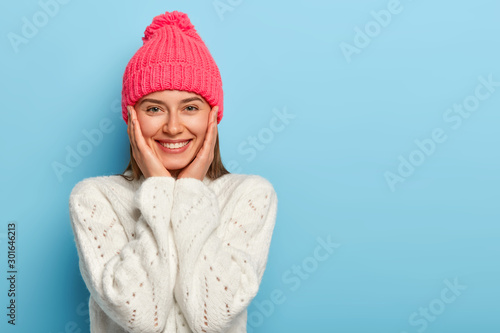 Fotografía Romantic positive young European woman smiles gently, has white perfect teeth, touches both cheeks, has friendly look, wears pink hat with pompon and white sweater, models against blue wall