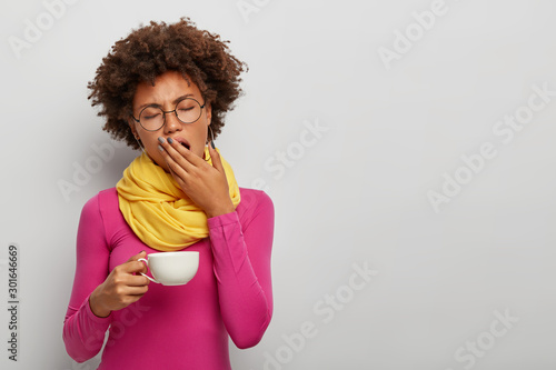 Photo  Tired curly woman yawn, has sleepy expression, drinks coffee early in morning, h