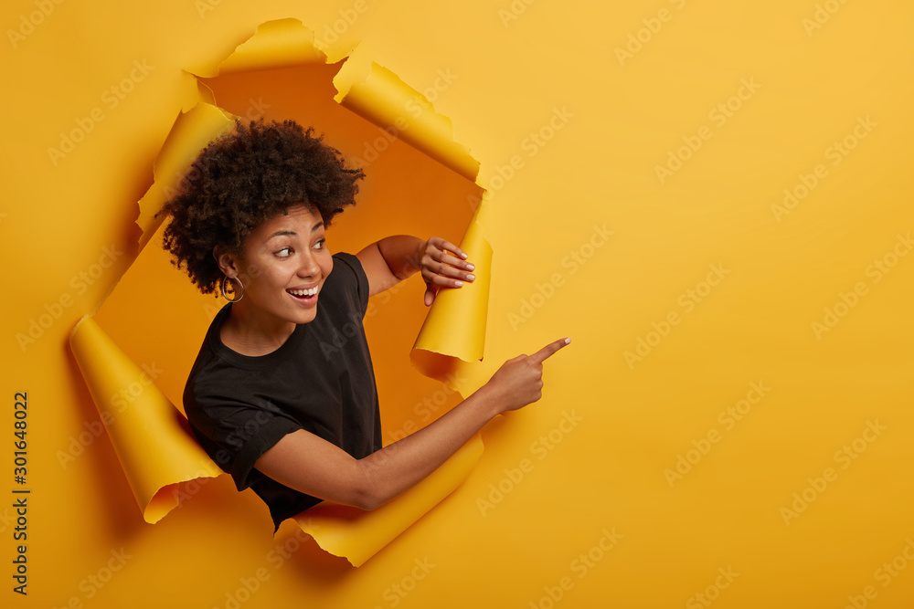 Fototapety, obrazy: Joyous friendly looking smiling girl points aside with happy expression, toothy smile, pleased to show awesome advertisement, dressed casually says use copy space wisely gestures through ripped paper