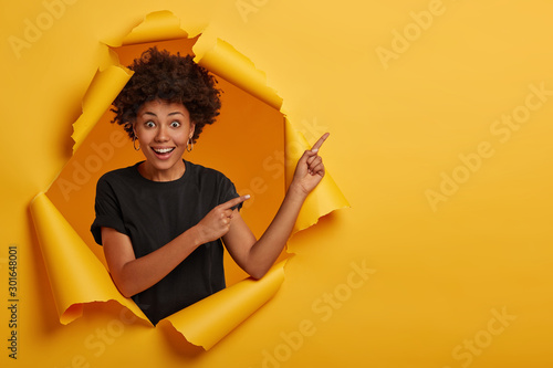 Fotografía  Nice attractive female model with crisp hair points aside, demonstrates advertisement, feels cheery and curious, wears black t shirt, stands in hole of paper wall shows yellow bright vivid copy space