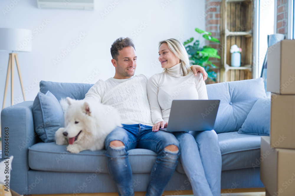 Fototapeta Young beautiful couple with dog sitting on the sofa using laptop at new home around cardboard boxes