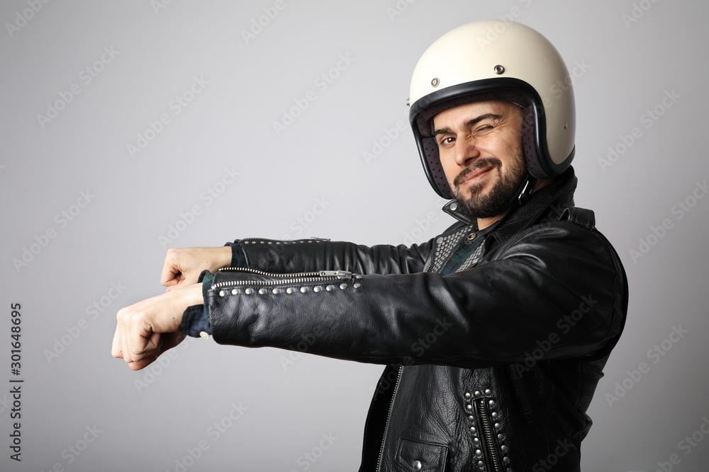 Fototapeta Portrait of biker with white helmet pretending ride his bike. Isolated.