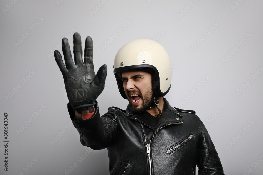 Fototapeta Close-up portrait of biker with white helmet making stop signs with his hand. Isolated.