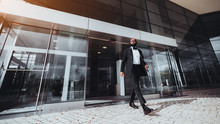 An Elegant Bearded Bald African Man Entrepreneur Is Leaving A Business Skyscraper, He Has Just Passed Automatic Sliding Doors; A Black Businessman In A Formal Suit Is Leaving A Modern Building