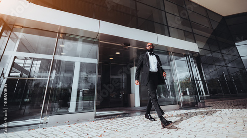 Fototapeta An elegant bearded bald African man entrepreneur is leaving a business skyscraper, he has just passed automatic sliding doors; a black businessman in a formal suit is leaving a modern building obraz