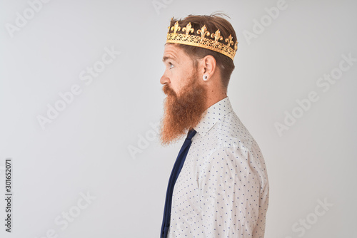 Fotomural  Young redhead irish businessman wearing crown king over isolated white background looking to side, relax profile pose with natural face with confident smile