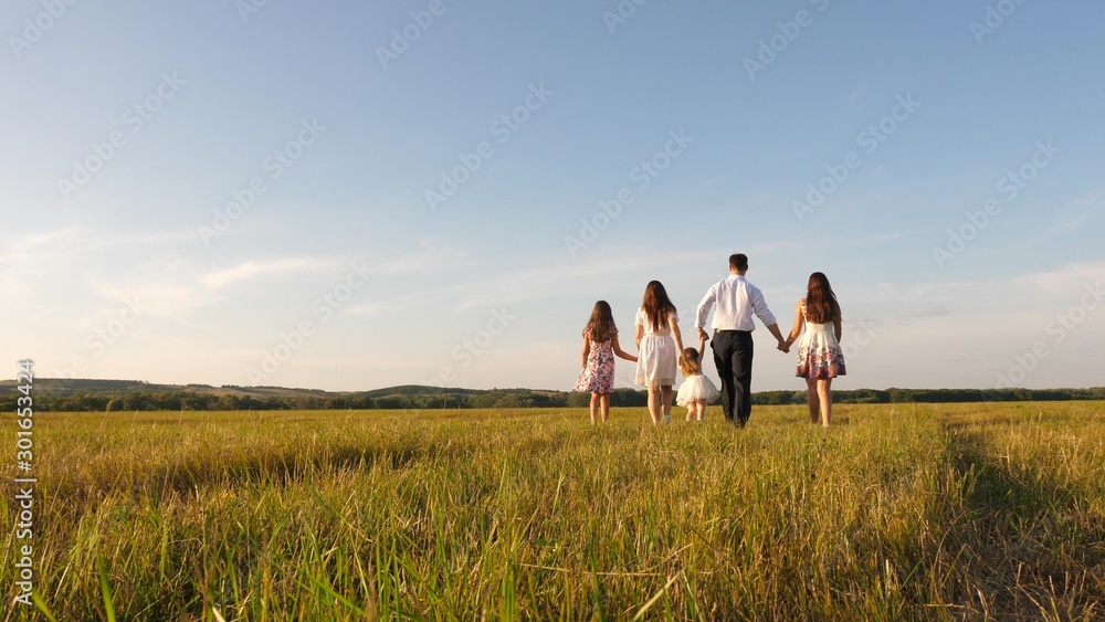 Fototapeta mother, father and little daughter with sisters walking in field in the sun. Happy young family. Children, dad and mom play in meadow in the sunshine. concept of happy family.