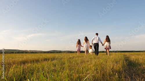 mother, father and little daughter with sisters walking in field in the sun. Happy young family. Children, dad and mom play in meadow in the sunshine. concept of happy family.