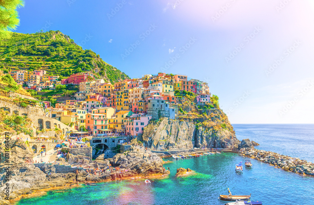 Fototapety, obrazy: Manarola traditional typical Italian village in National park Cinque Terre, colorful multicolored buildings houses on rock cliff, fishing boats on water, blue sky background, La Spezia, Liguria, Italy