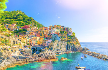 Manarola traditional typical Italian village in National park Cinque Terre, colorful multicolored buildings houses on rock cliff, fishing boats on water, blue sky background, La Spezia, Liguria, Italy
