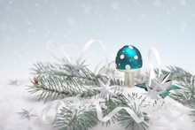 Turquoise Metallic Green Blue Mushroom Magic Toad Stool And White Paper Serpentine On White Background With Natural Fir Twigs Under Snow. Merry Xmas And A Happy New Year!