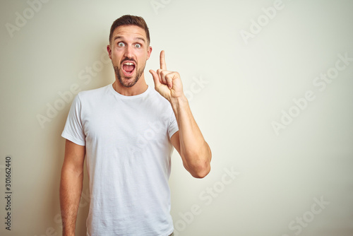 Fotomural Young handsome man wearing casual white t-shirt over isolated background pointing finger up with successful idea