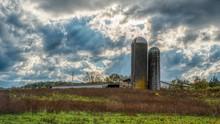 Two Silos In A Field On A Farm...