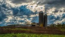 Two Silos In A Field On A Farm On A Stormy Day