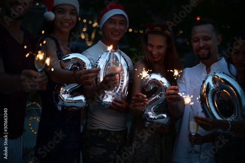 Fototapeta  Group of happy people of mixed race friends celebrate Christmas and New Year at a tropical resort in Santa hats with shiny numbers in their hands