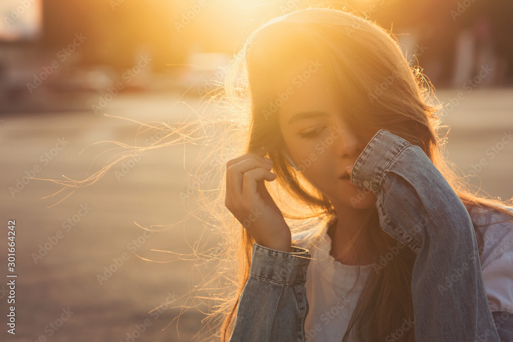 Fototapety, obrazy: Back light portrait of a happy single teen girl breathing fresh air in a city street during a sunny day at sunset in a park with a warm yellow light and urban background. Summertime. Lifestyle.