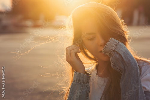 Back light portrait of a happy single teen girl breathing fresh air in a city street during a sunny day at sunset in a park with a warm yellow light and urban background. Summertime. Lifestyle. #301664242