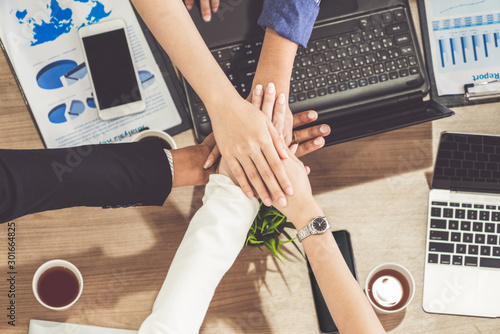 Fotomural  Businessmen and businesswomen joining hands in group meeting at multicultural office room showing teamwork, support and unity in business