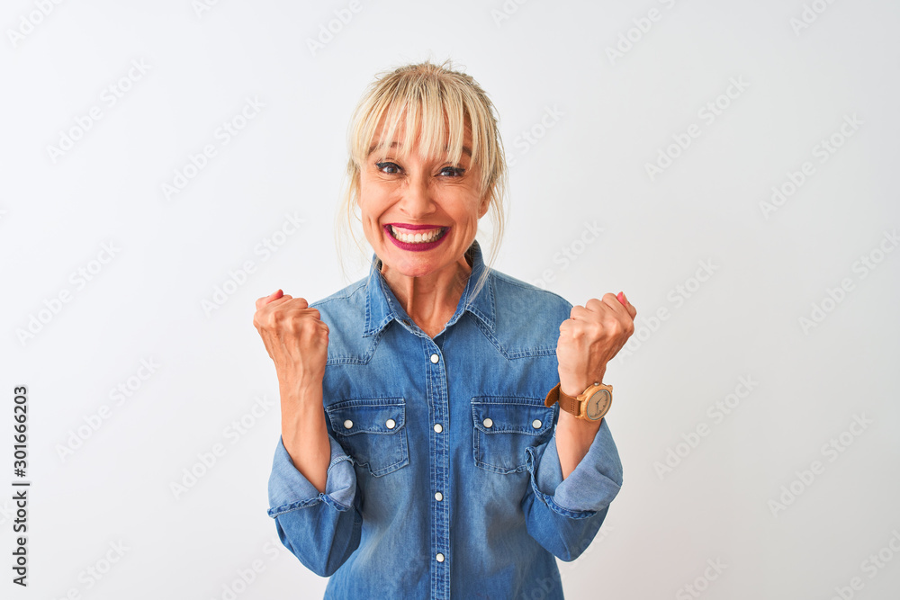 Fototapeta Middle age woman wearing casual denim shirt standing over isolated white background celebrating surprised and amazed for success with arms raised and open eyes. Winner concept.