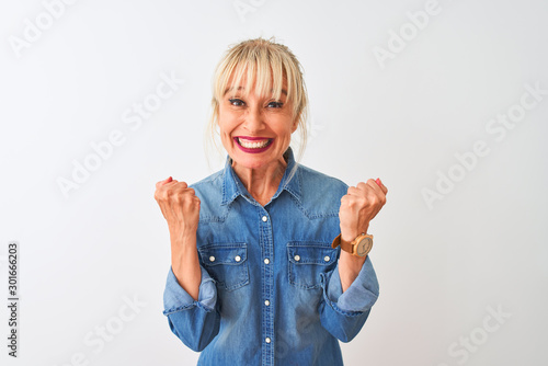 Obraz Middle age woman wearing casual denim shirt standing over isolated white background celebrating surprised and amazed for success with arms raised and open eyes. Winner concept. - fototapety do salonu