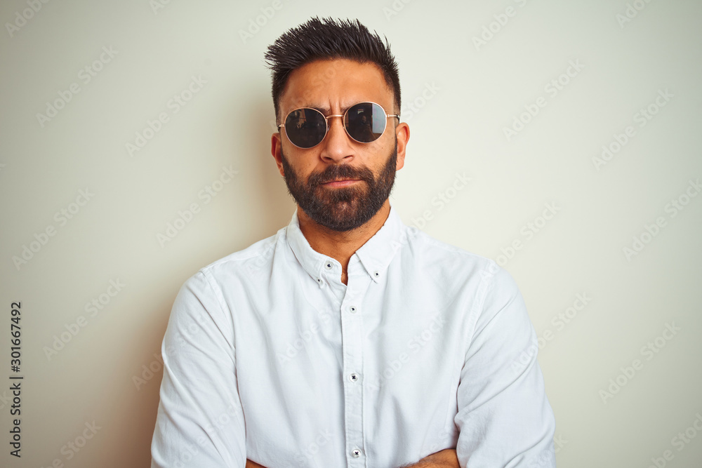 Fototapeta Handsome indian buinessman wearing shirt and sunglasses over isolated white background skeptic and nervous, disapproving expression on face with crossed arms. Negative person.