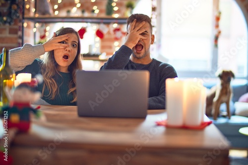 Young beautiful couple sitting using laptop around christmas decoration at home peeking in shock covering face and eyes with hand, looking through fingers with embarrassed expression.