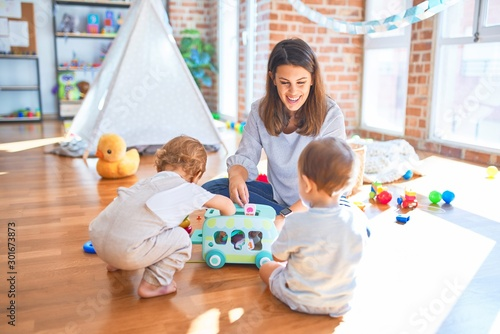 Beautiful teacher and toddlers playing around lots of toys at kindergarten Wallpaper Mural
