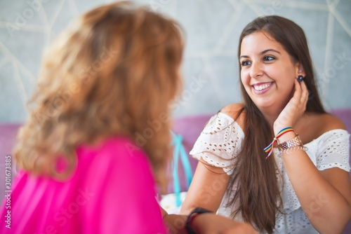 Photo  Beautiful mother and daugther sitting at restaurant speaking and smiling