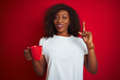 Young african american woman drinking cup of coffee over isolated red background surprised with an idea or question pointing finger with happy face, number one