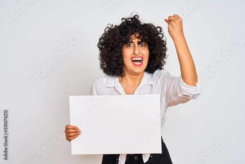 Fotomural  Young arab woman with curly hair holding banner over isolated white background a