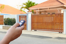 Closeup Hand Holding And Using Remote Control To Open Or Close The Automatic Wooden Gate With Home Blurred Background. Home Remote Control Concept. Concept.