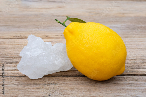 Photo Crystal alum stone and fresh organic yellow lemon lime fruit with green leaf  isolated on wood table background