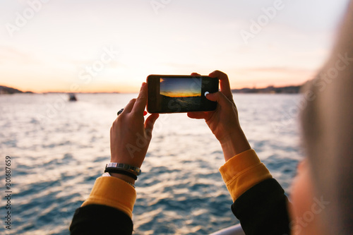 Hand holding black smartphone taking a photo of Bosphorus Strait at sunset light, golden hour. Nature and journey concept #301687659