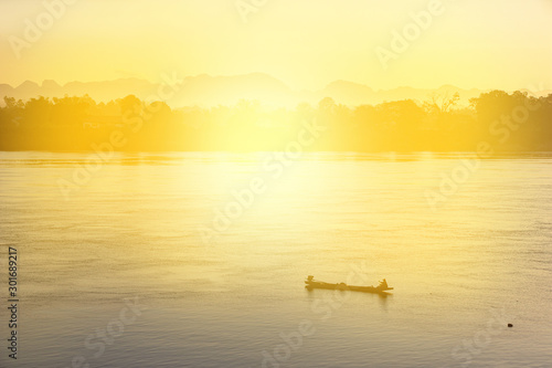 Foto auf Leinwand Gelb Schwefelsäure silhouette fisherman boat in sunrise at Mekong River in Thailand, peacefulness in nature.