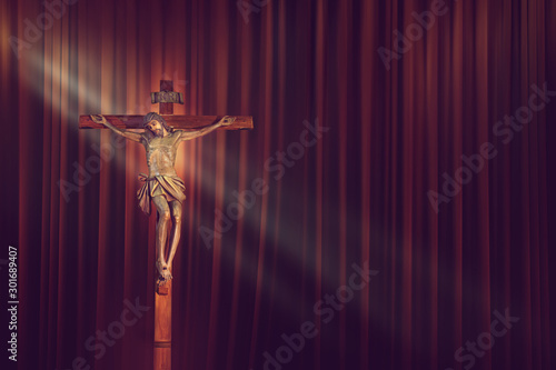 Fototapeta  crucifix, jesus on the cross in church with ray of light on red curtain backgrou