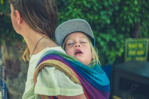 Young mother carrying sleeping toddler in sling on her back