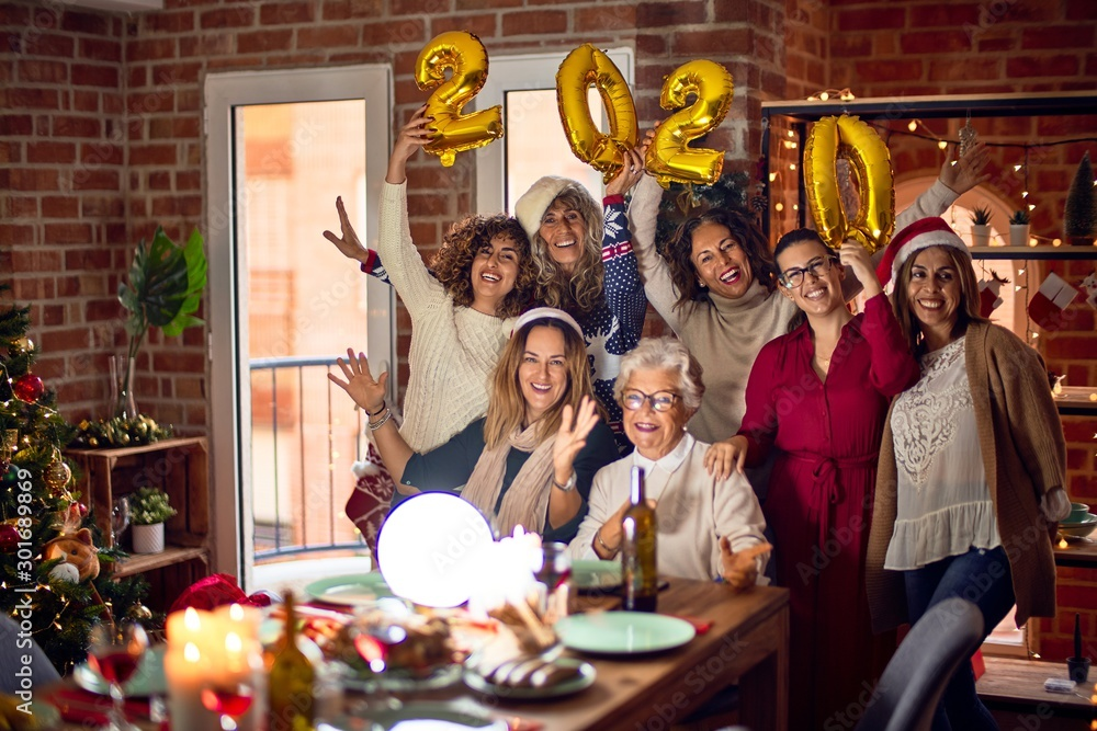 Fototapety, obrazy: Beautiful group of women smiling happy and confident. Posing around christmas tree holding 2020 ballons at home